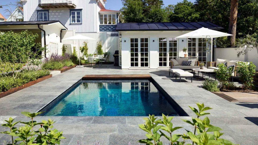 En terrasse er belagt med utefliser av Offerdalskifer. Terrassen har et svømmebasseng, parasoll og solsenger i forkant av et idyllisk hvitt badehus.