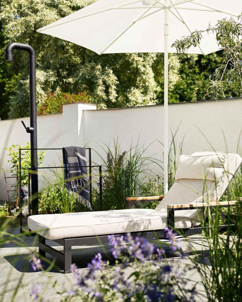 En vakker terrasse belagt med uteflis av Offerdalskifer. Terrassen er møbler med en solseng g parasoll og den er vakkert beplantet