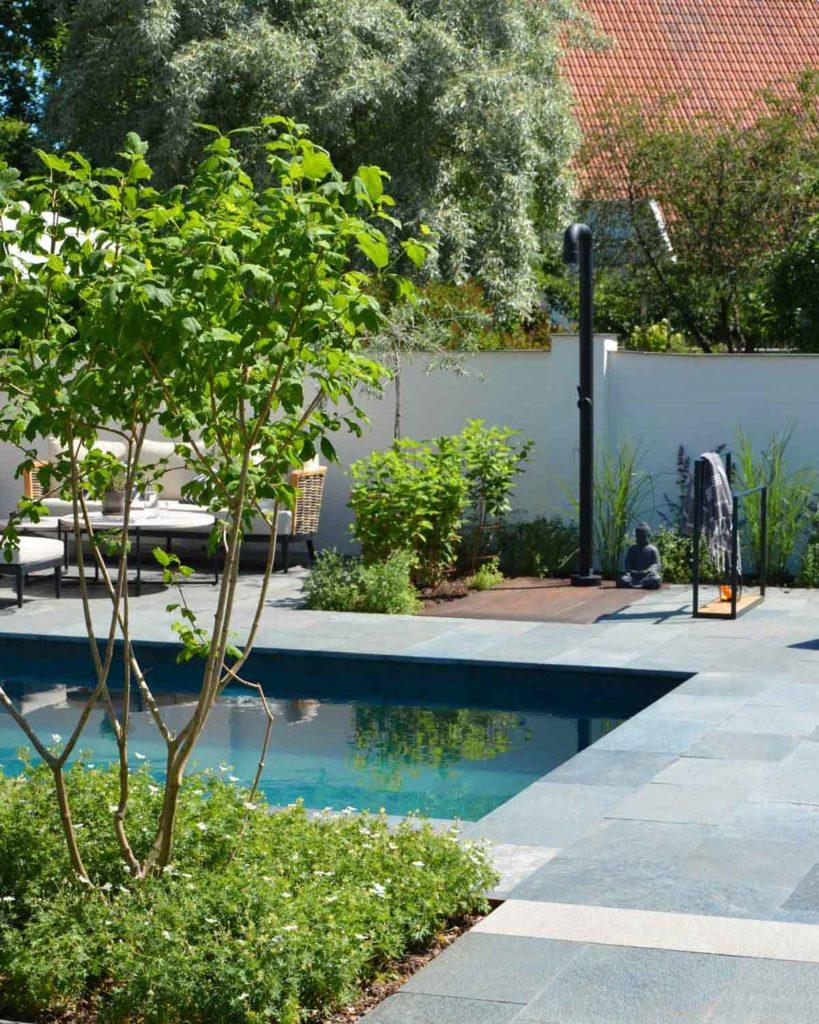 En terrasse er belagt med utefliser av Offerdalskifer. Terrassen har et svømmebasseng, vakker beplantning, utedusj og solsenger.