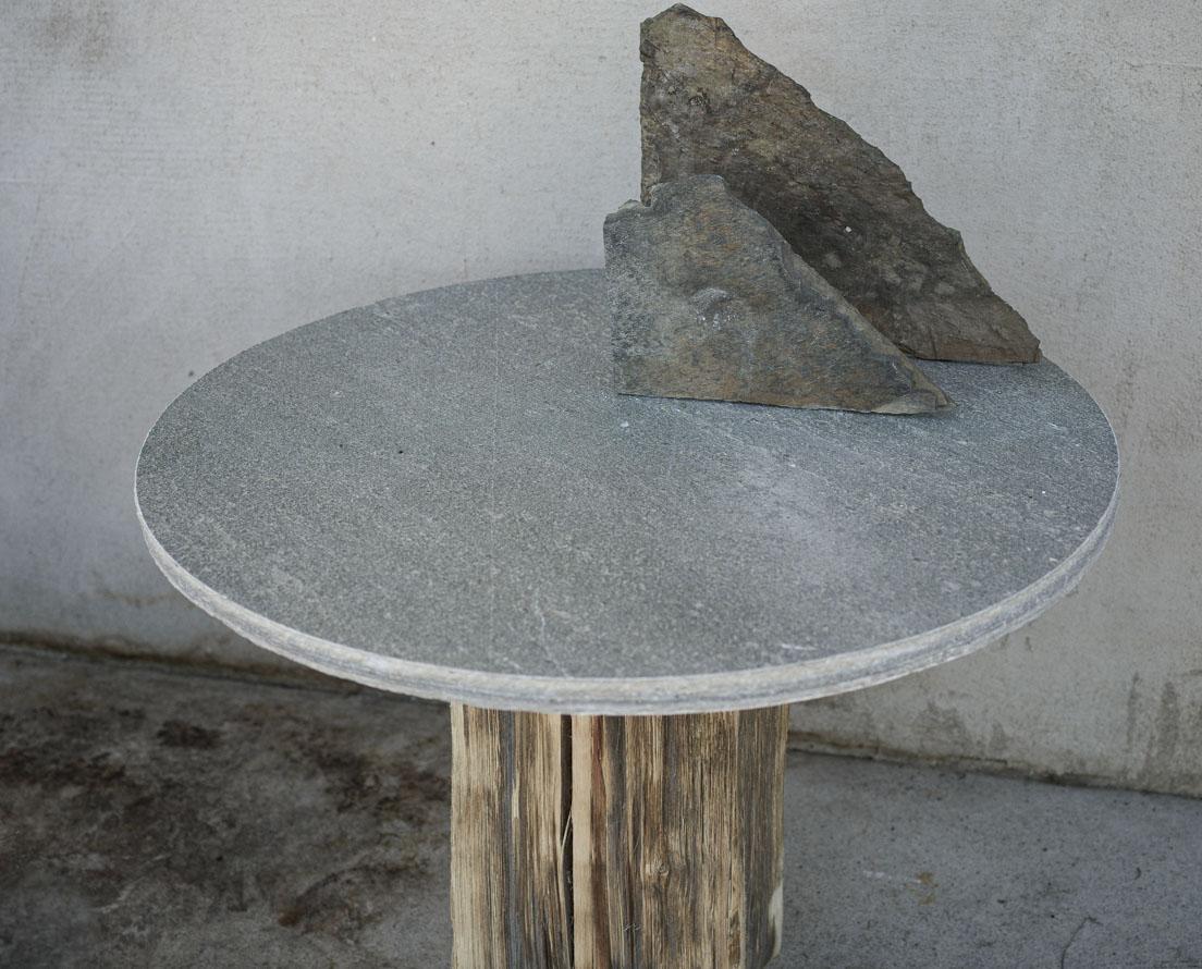 Et rundbord i Oppdalskifer med en stubbe som fot og med steiner som skulpturelement på bordplaten