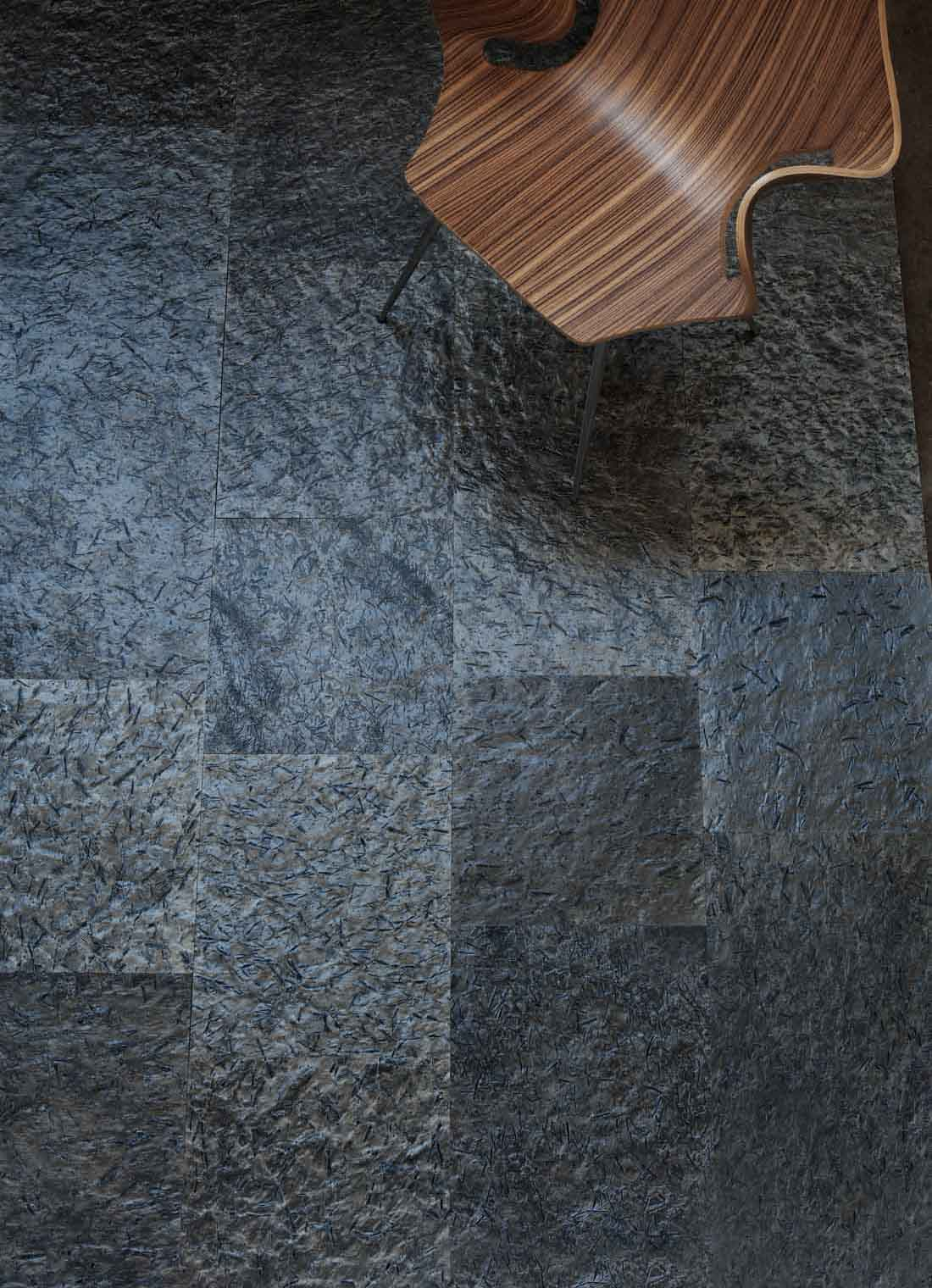 Et gulv belagt med slipte fliser lav Ottaskifer med en designstol i tre
