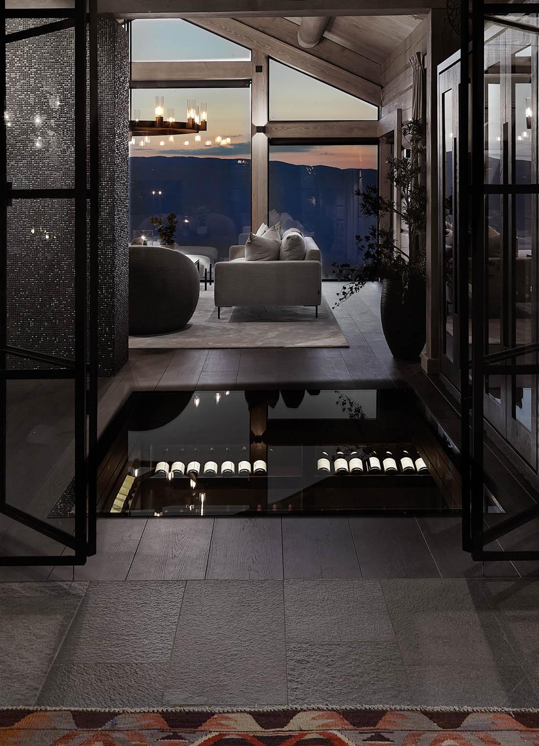 Hytte med fliser av Offerdalskifer i entreen og en stor glassplate i gulvet som gir innsyn til vinkjeller.