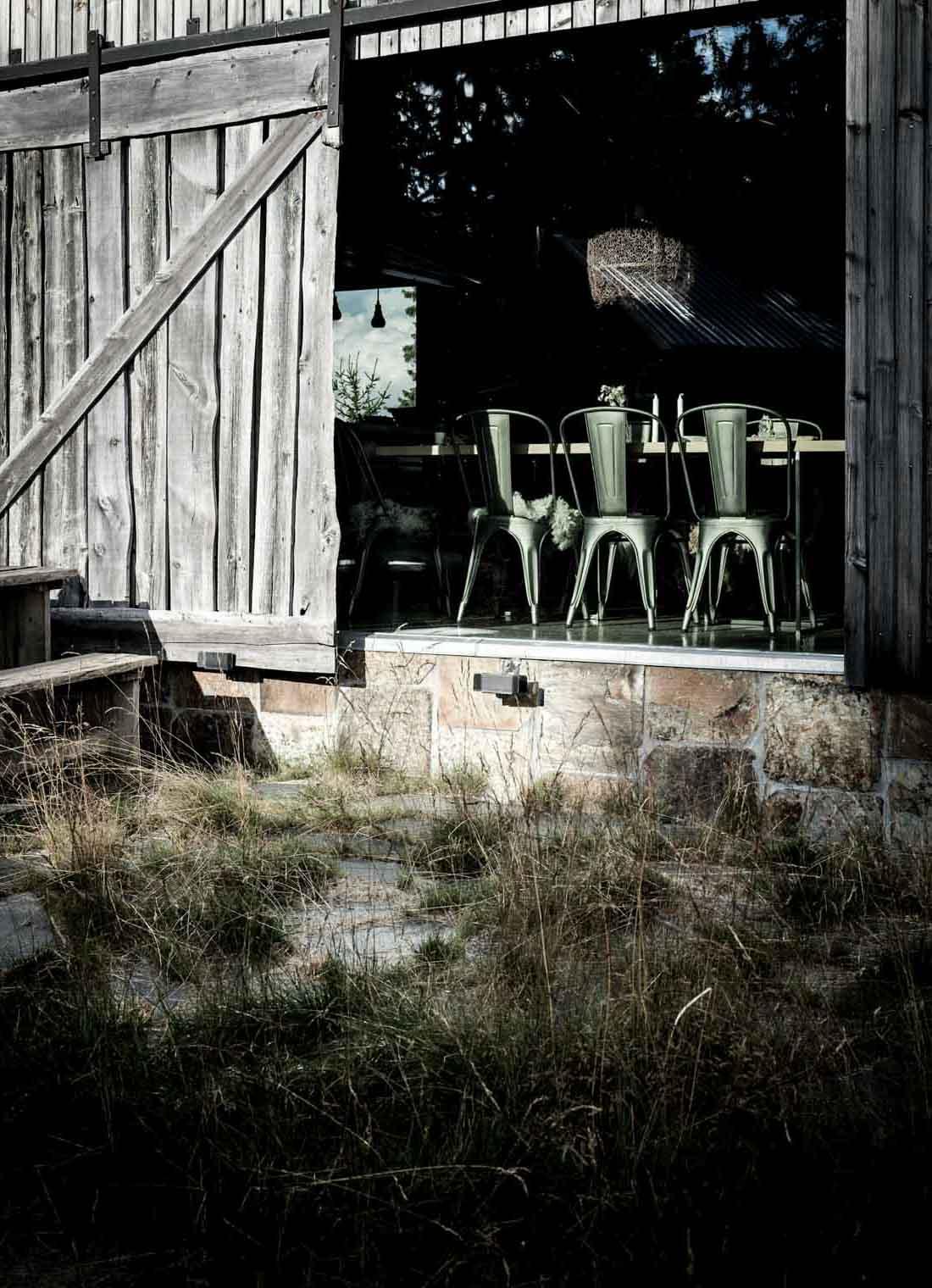 En hytte med gjenbrukt av Ottaskifer rust på grunnmur og trematerialer. Dørene er åpen inn til en moderne møblert spisestue.
