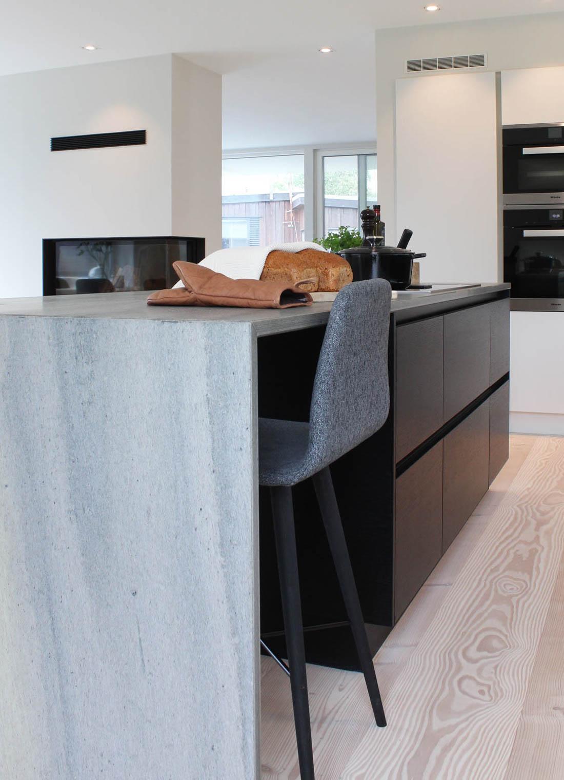 Et moderne kjøkken med en kjøkkenbenk i lys Oppdal silkebørstet skifer med fossefalldesign - at benken fortsetter ned til gulvet.