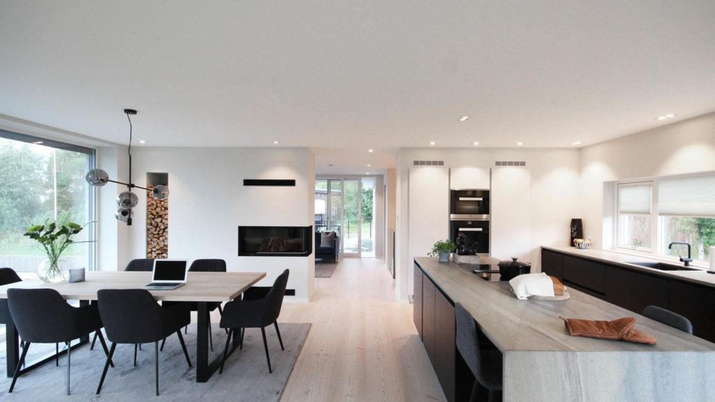 Et lyst moderne hjem med åpen kjøkken, spisestue og stue med benkeplater i lys Oppdal silkebørstet skifer. Steinplatener i lyse gråsjatteringer som står godt til tregulvet og er en fin kontrast til den mørke kjøkkeninnredningen.