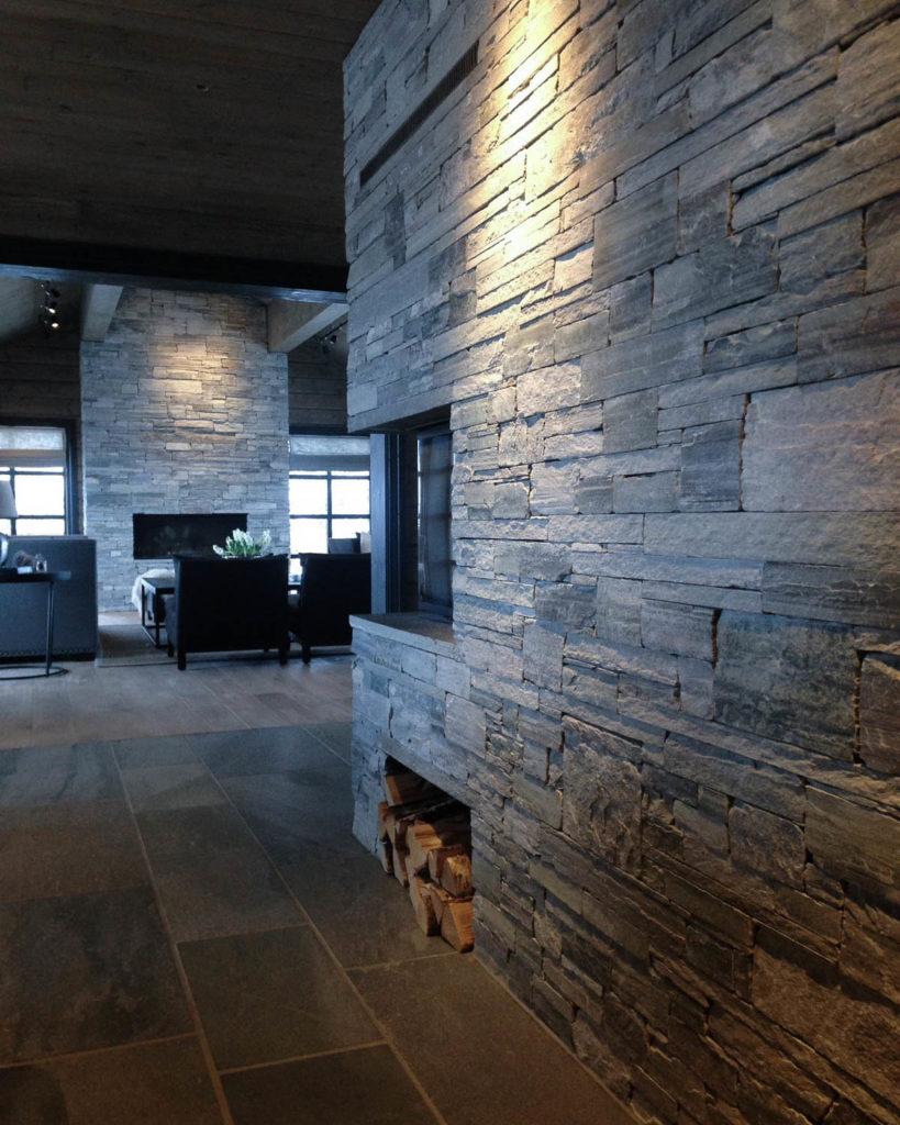 En hytte med en peis av Lys Oppdal skifer murstein tørrmur. Gulvet er av fliser av Lys Oppdalskifer.