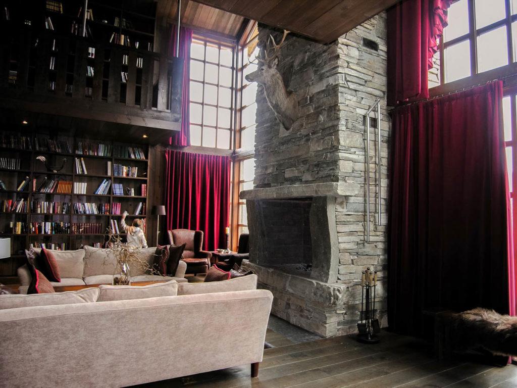 En hytte med en peis av Lys Oppdal skifer murstein tørrmur. Stuen har høye bokhyller fra gulv til tak og tunge dyprøde gardiner