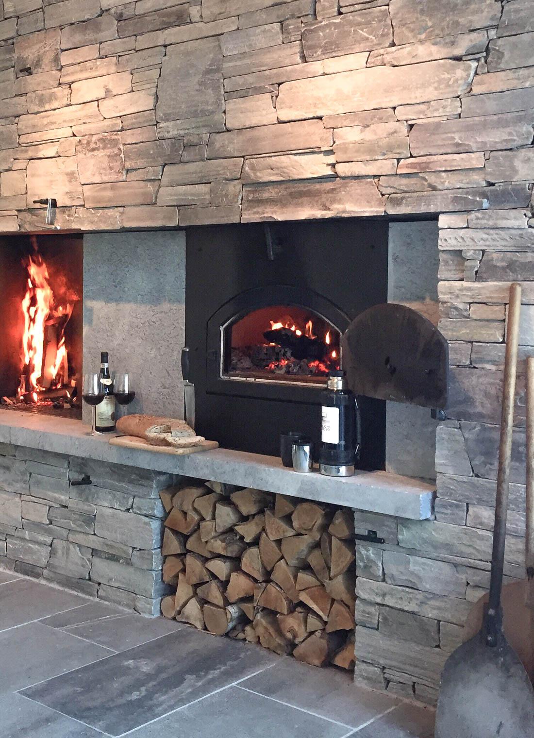 En pizzaovn og peis murt med lys Oppdalskifer tørrmur. Det brenner i både bakerovnen og peisen.
