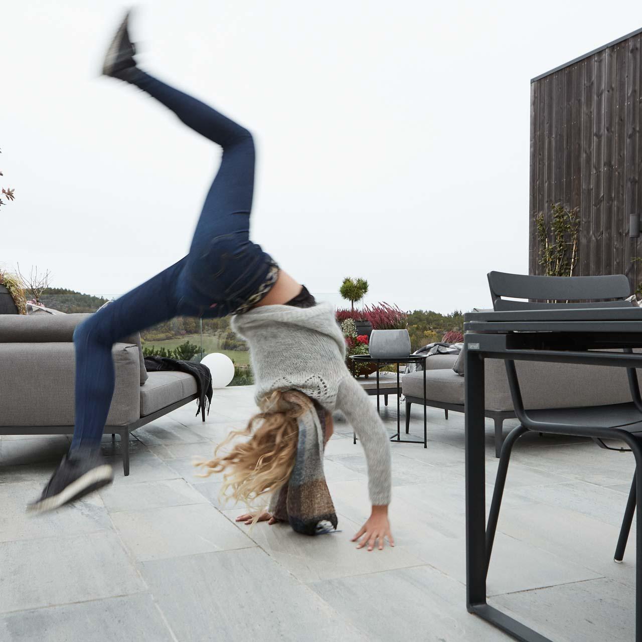 En ung jente slår hjul på en stor terrasse belagt med utefliser i antikkbørstet lys Oppdalskifer