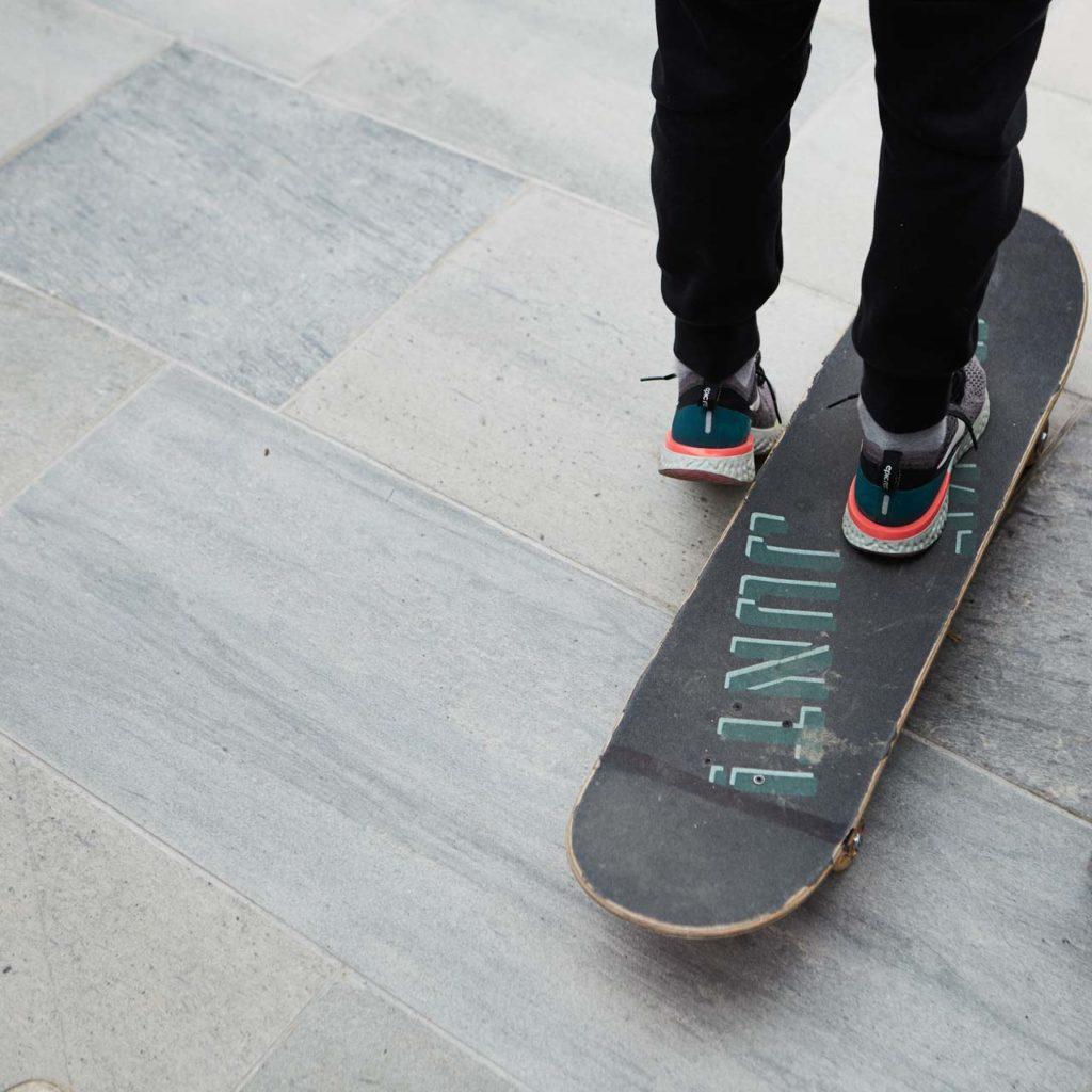 Føttene til en gutt som står på skateboard på en stor terrasse belagt med utefliser i antikkbørstet lys Oppdalskifer