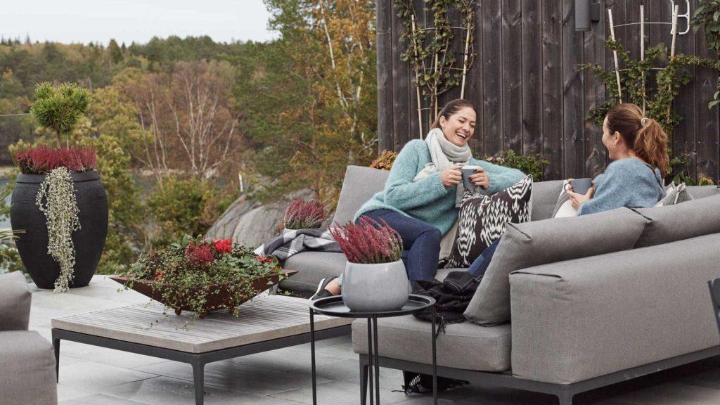 2 damer som sitter og prater, ler og drikker kaffe på en stor terrasse belagt med uteflis i lys Oppdalskifer