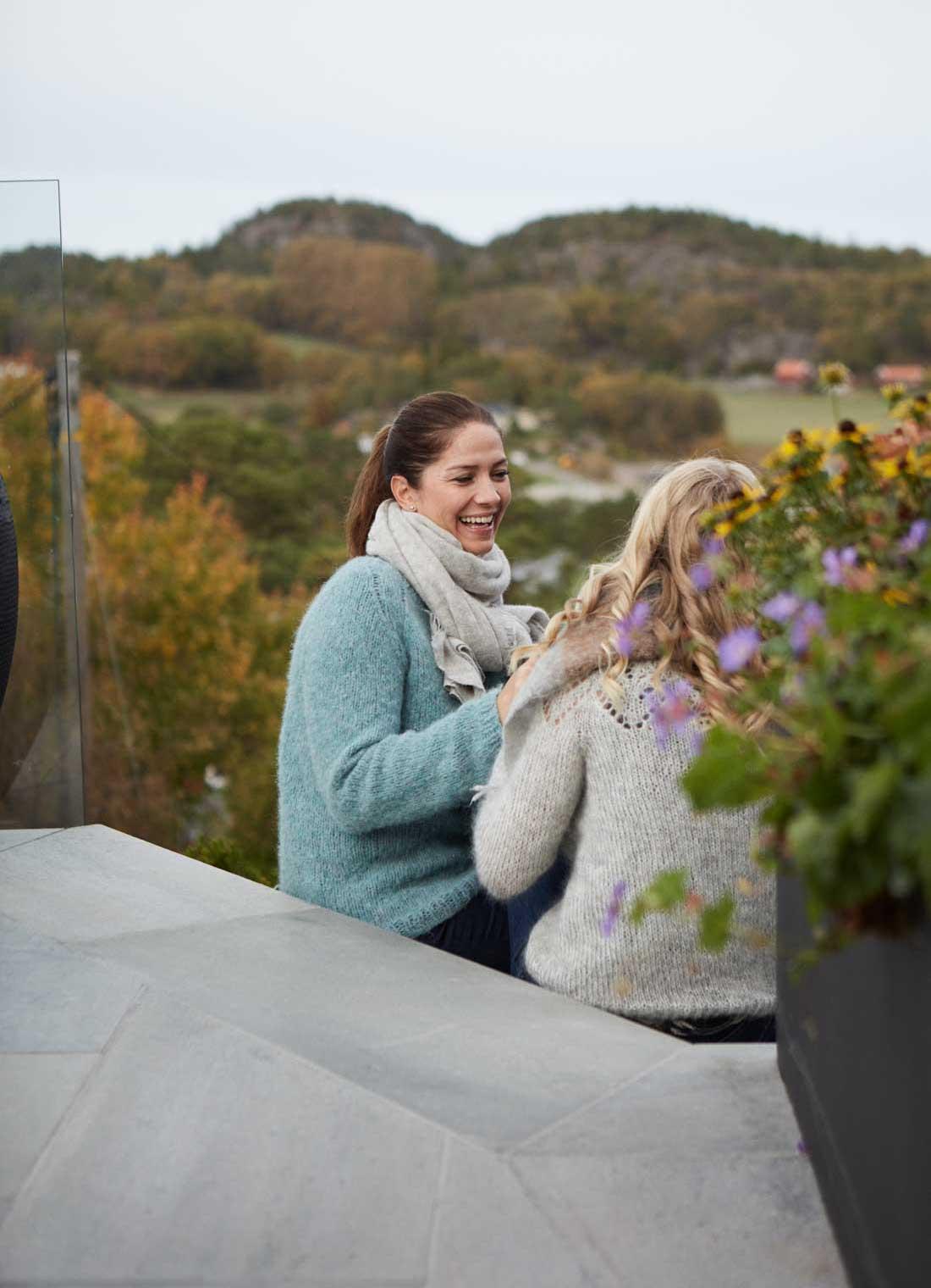 En kvinne og ung jente som sitter i trappen på en terrasse belagt med uteflis i lys Oppdalskifer. Det er grønt og frodig rundt og med store blomsterpotter på terrassen.