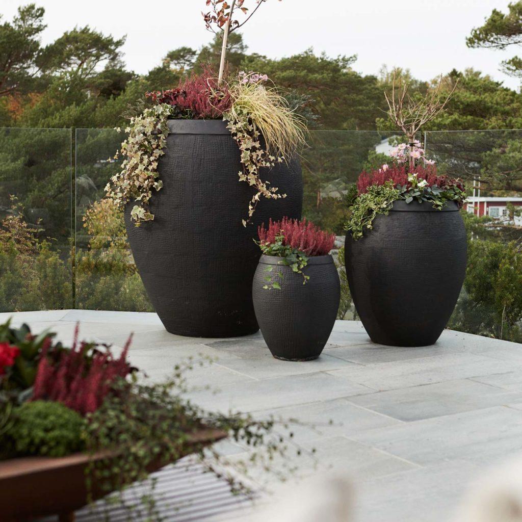 Store krukke med blomster som står på en terrasse med lys Oppdal utefliser i skifer