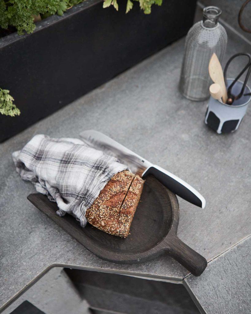 Et utekjøkken med en benkeplate i antikkbørstet lys Oppdalskifer med et brød og en brødkniv