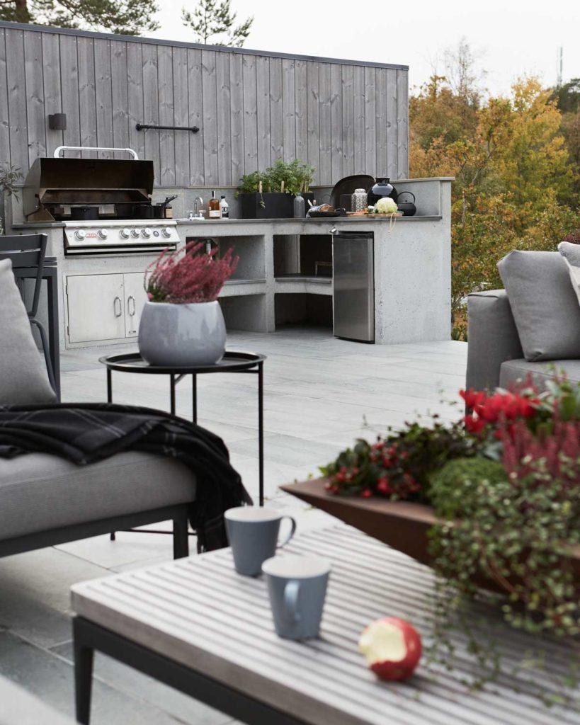 En stor terrasse belagt med lys Oppdal uteflis og hvor en ser et utekjøkken i bakgrunnen