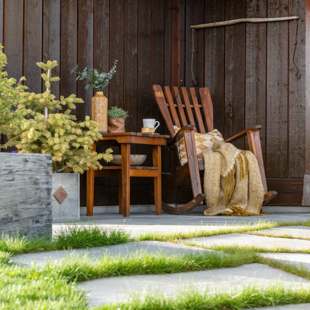 En uteplass på en laftet hytte med gyngestol med puter og lys Oppdal bruddskifer på bakken.