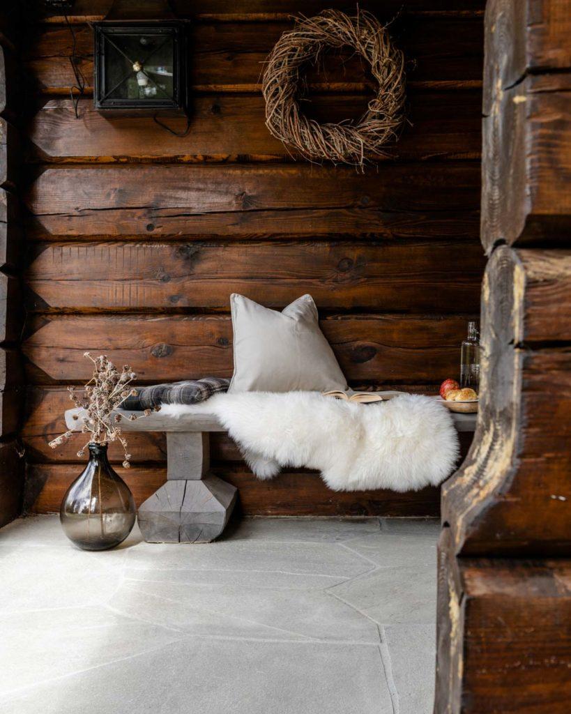 Et inngangsparti på en laftet hytte med en benk med puter og lys Oppdal bruddskifer på bakken.