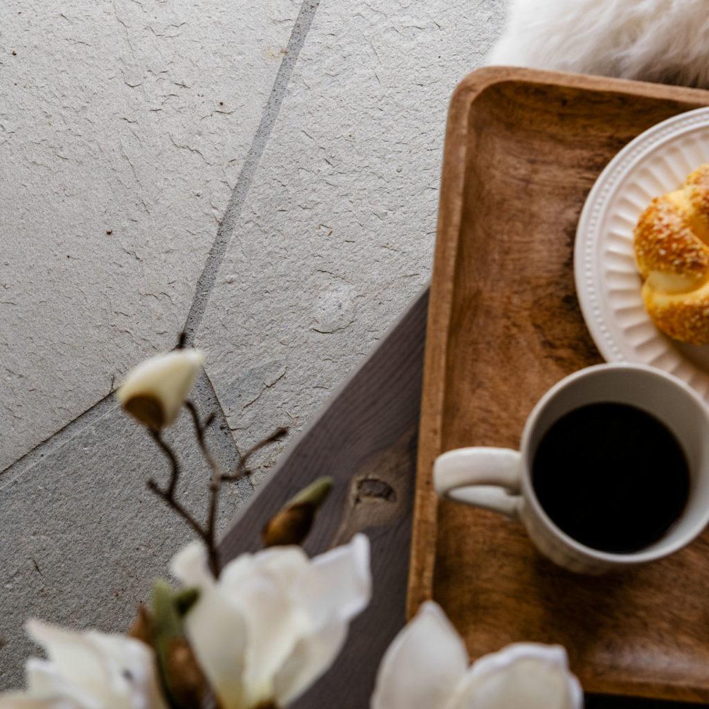 Et brett med kaffe og kaker servert på en uteplass med lys Oppdal bruddskifer