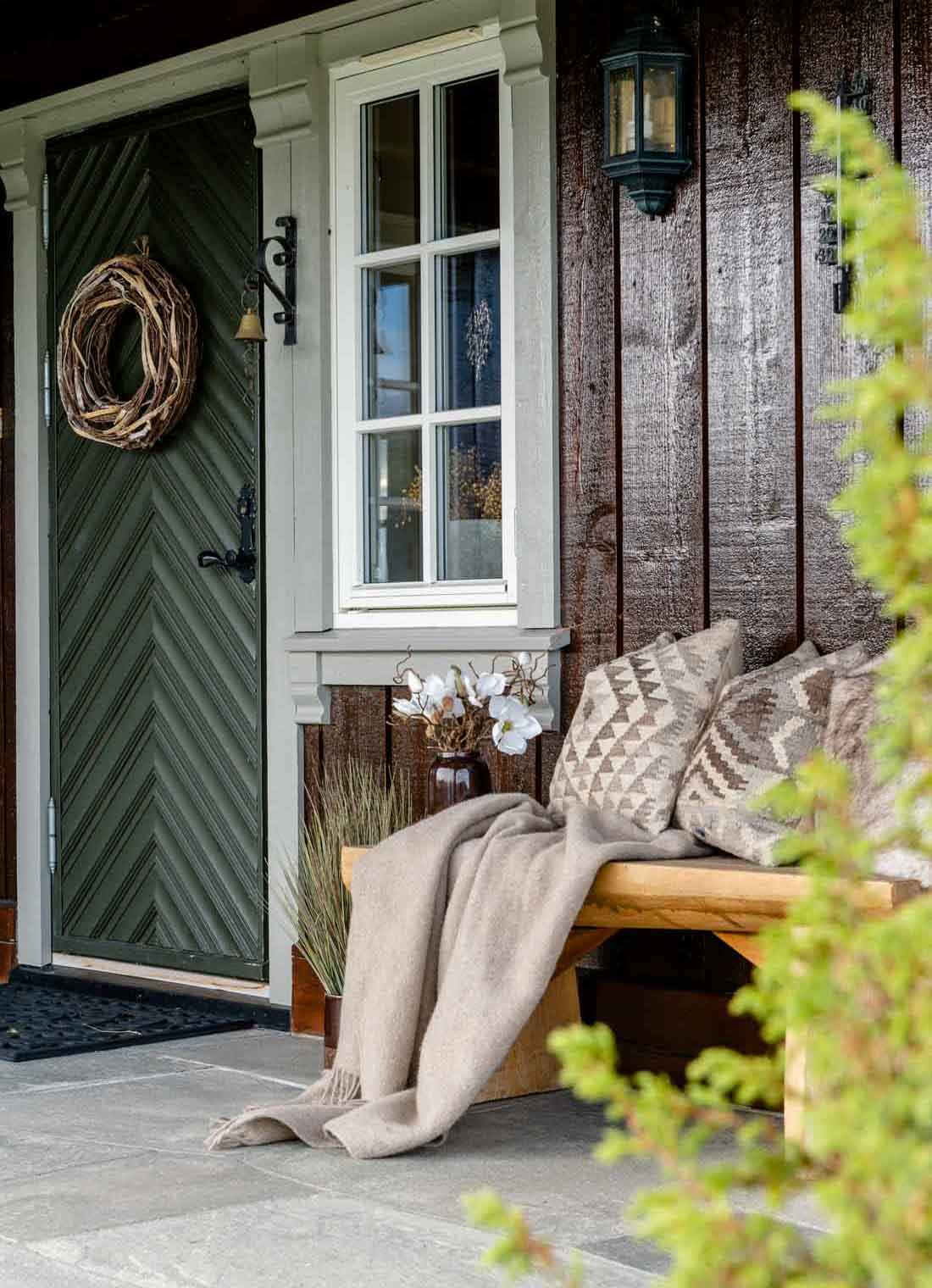 Et utvendig inngangsparti på en laftet hytte med en benk med puter. Bakken er kledt med grå bruddskifer av Oppdalskifer.