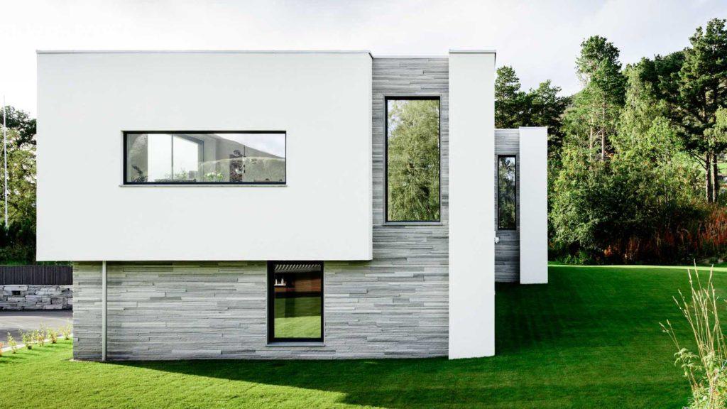 Et funkishus med lys Oppdalskifer murstein REN i kombinasjon med glatt murpuss. Det er sommer og grønn plen utenfor.