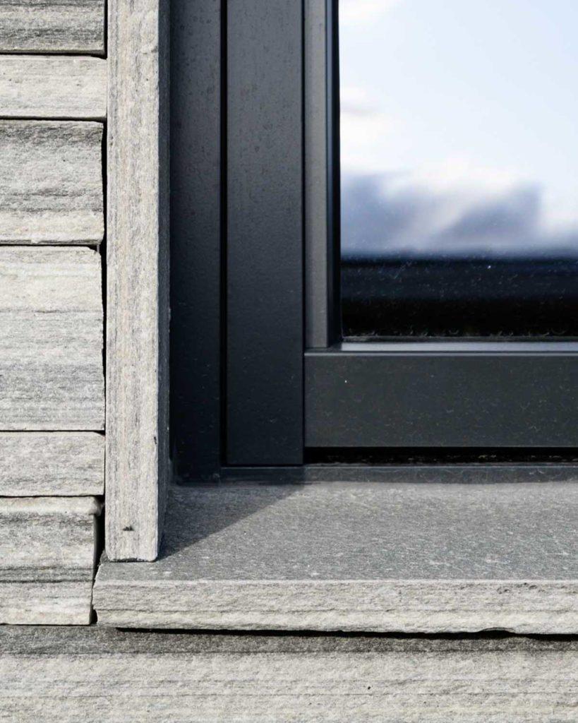 Et hjørne på et hus som har murstein av lys Oppdalskifer REN på fasaden og samme skifer som vindusbrett