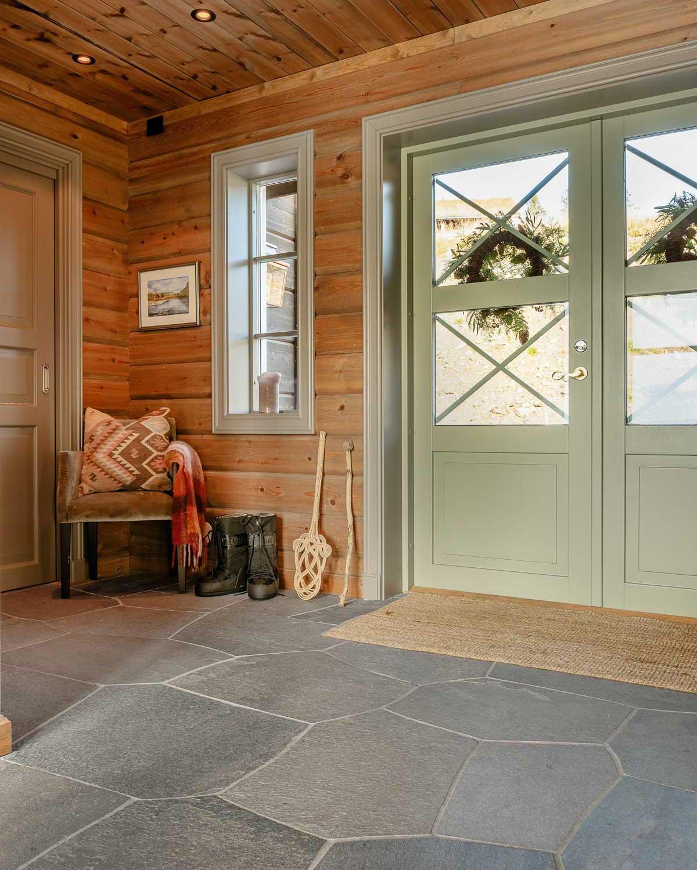 En entre på en hytte med en stor grønn dobbel inngangsdør med glassvindu. Gulvet er kledt med grå bruddskifer av Oppdalskifer.