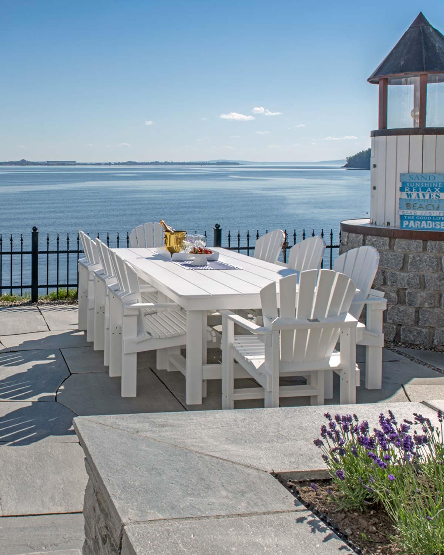 Terrasse ved sjøen med bruddskifer og skiferplater rundt blomsterbed. Lys grå Oppdalskifer og hvite hagemøbler gir et sommerlig uttrykk.