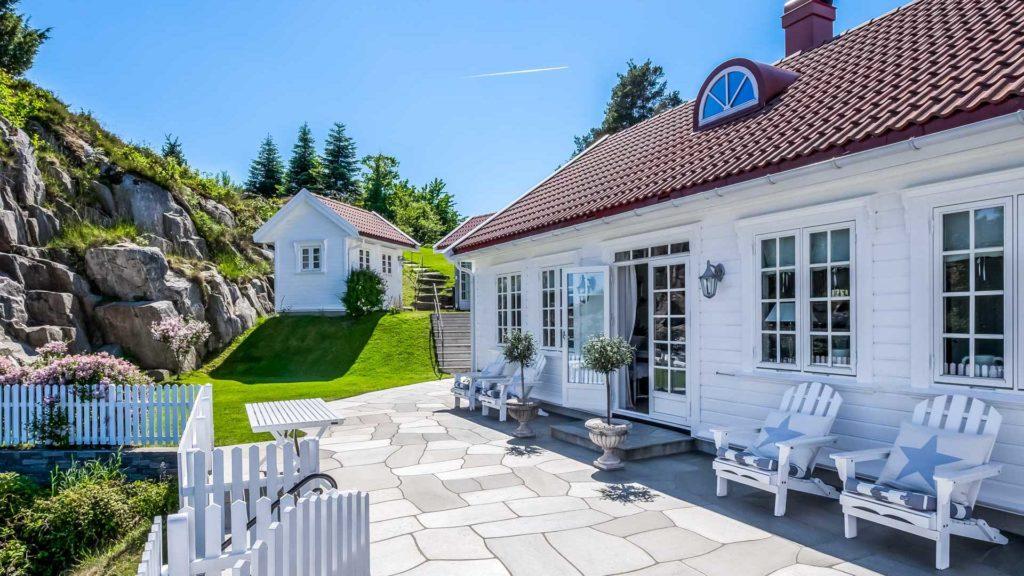 En stor uteplass/terrasse ved en hvit hytte ved sjøen belagt med lys Oppdal bruddskifer. På uteplassen er det vakre tremøbler og rundt er det grønn plen.