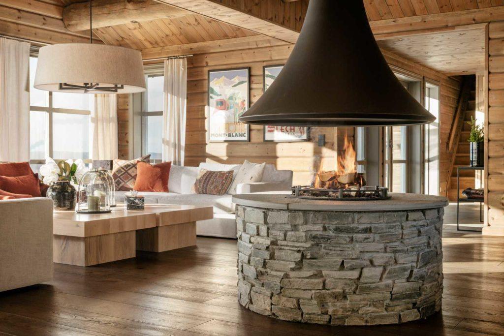 Rund peis i hytte, midstilt i rommet med sofaområde i bakgrunnen