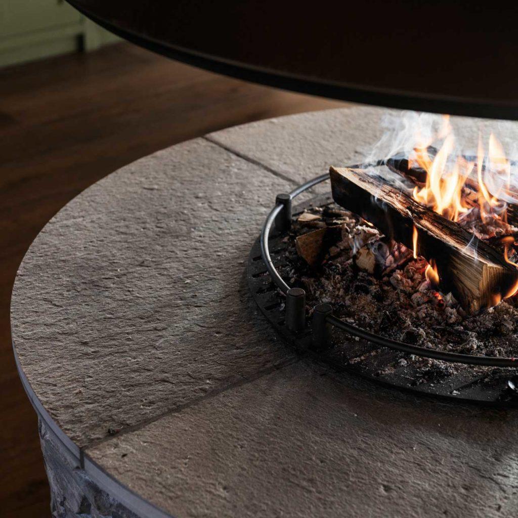En rund peis på hytte i murstein og med plater avdekning på toppen av lys Oppdalskifer.