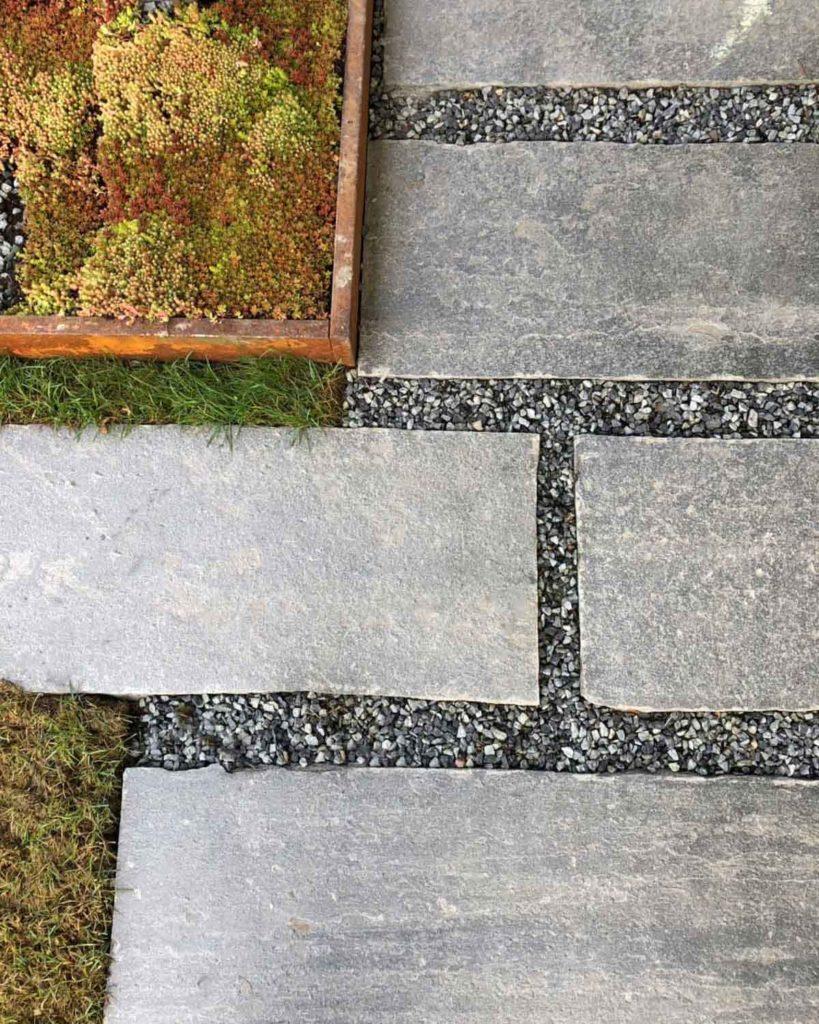 Tråkkheller i lys Oppdalskifer lagt i mønster med grus mellom hellen. Et bed med takløk er plassert ved siden.
