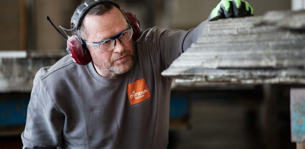 En steinhugger analyserer skiferblokken av Oppdalskifer før han begynner bearbeidingen.
