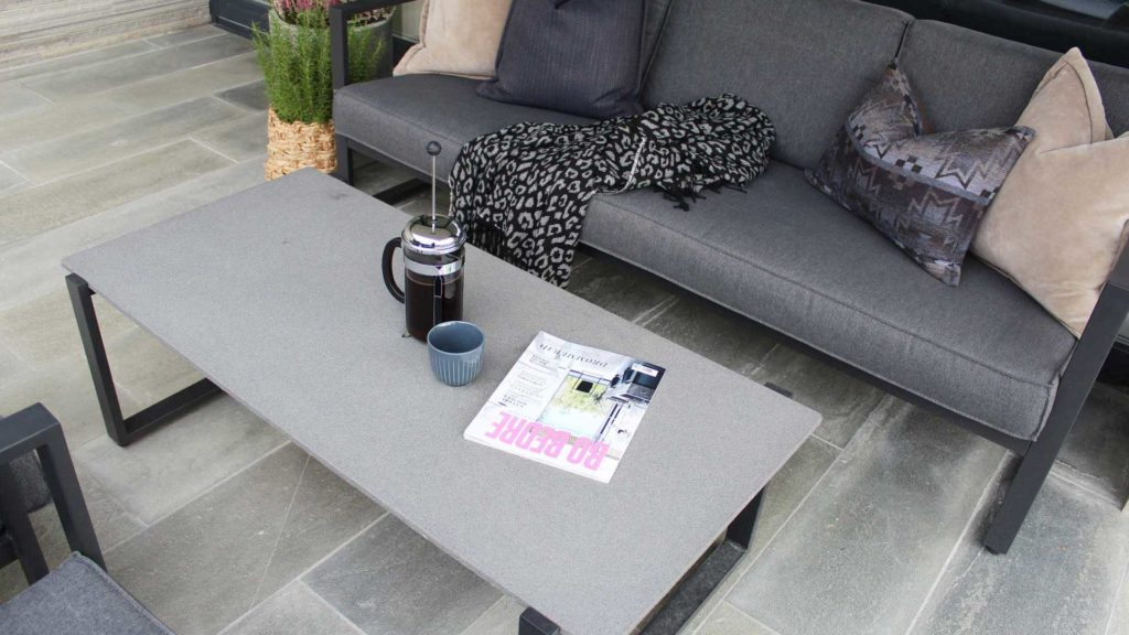 En terrasse med lys Oppdalskifer uteflis og møblert med sofa og bord. På bordet er det kaffekane og et interiørmagasin.