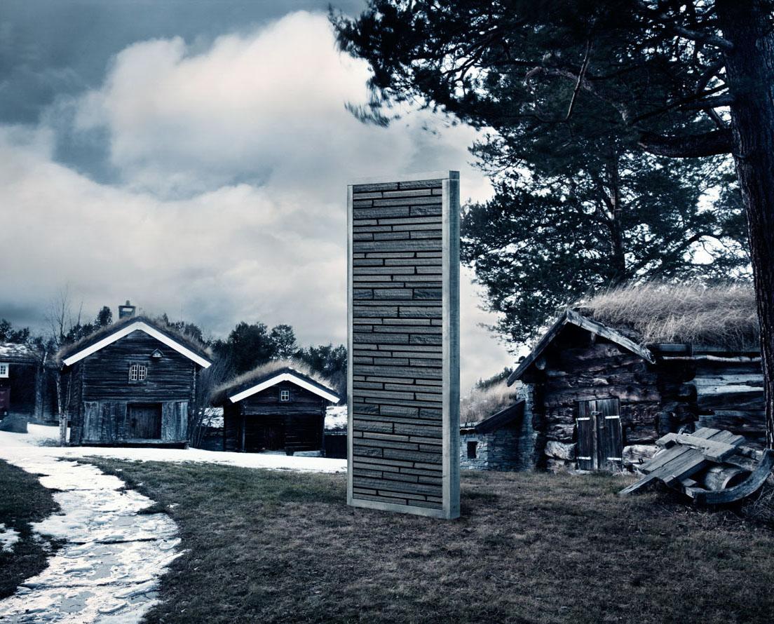 En metallramme med murstein av typen Minera Rustikk av lys Oppdal skifer står på et tun med flere laftede bygninger
