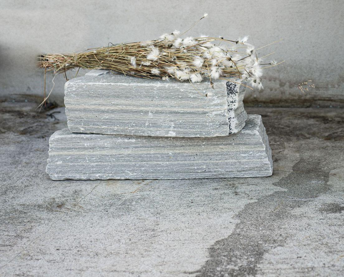 To murstein av Lys Oppdal skifer kalt råkopp eler tørrmur ligger stablet oppå hverandre med en bunt strå med blomster oppå