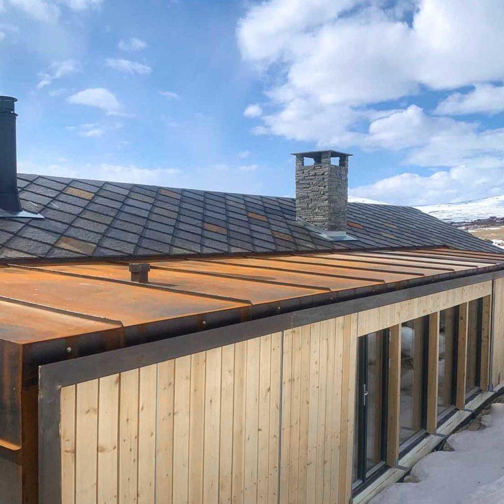 Et moderne tak på en hytte med firkantheller av Otta takskifer i gyldne fargetoner.
