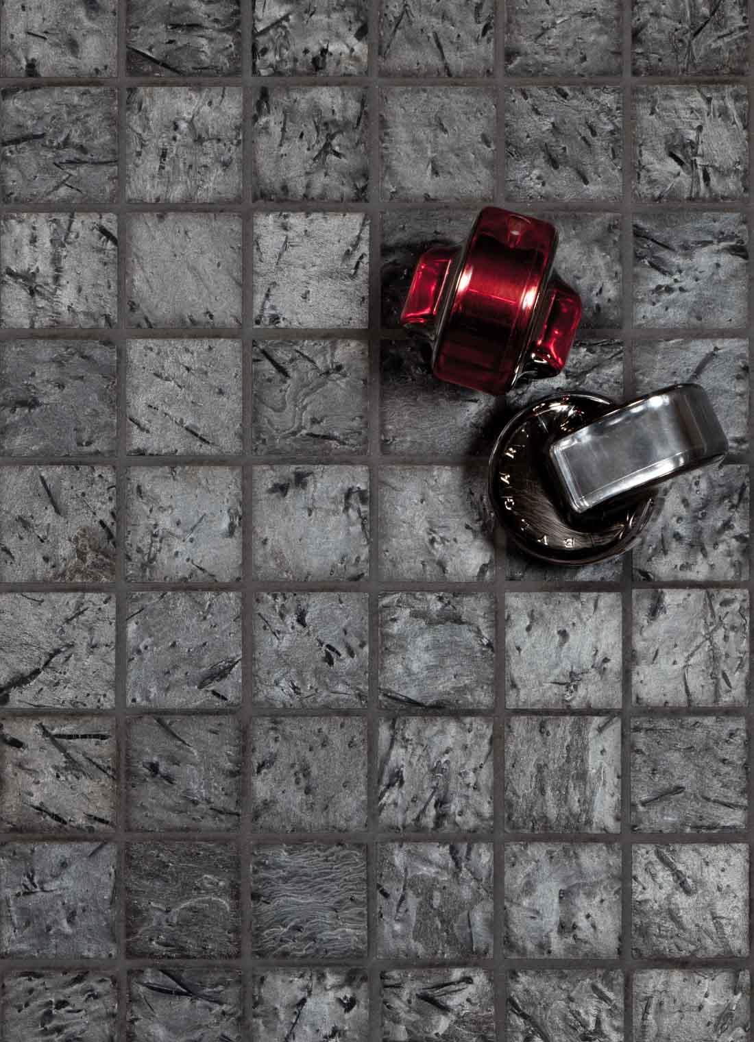 Mosaikkfliser på et bad av slipt Ottaskifer med to parfymeflaske liggende på flisene