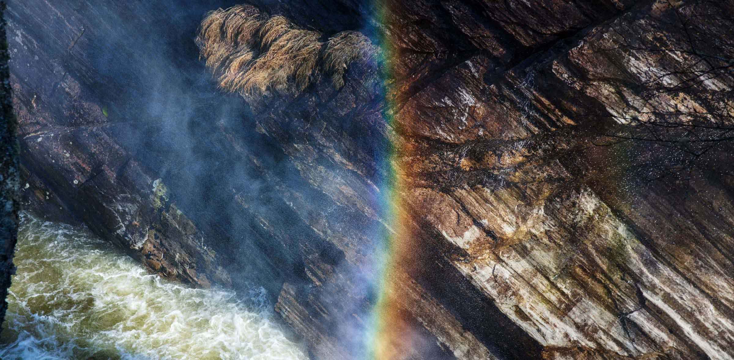 Et naturbilde fra skiferbruddet Otta Pillarguri. Skiferen er rustfarget og en regnbue dannes fra elven under berget.