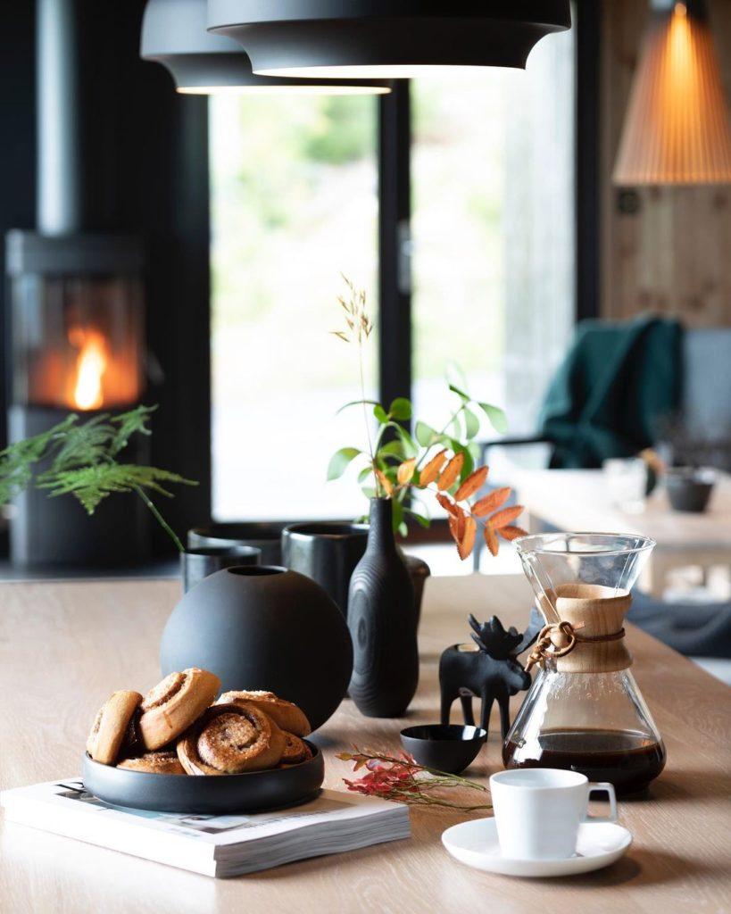 En lun stue på en fjellhytte med mange mørke detaljer som kompletterer den mørke Ottaskiferen i entreen. Bordet er dekket og det brenner ii vedovnen.