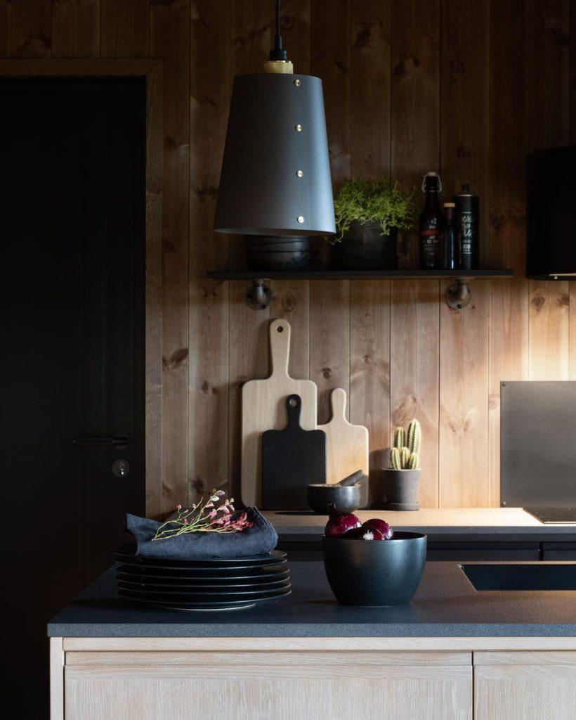 Et lunt hyttekjøkken med mange mørke detaljer som kompletterer den mørke Ottaskiferen i entreen