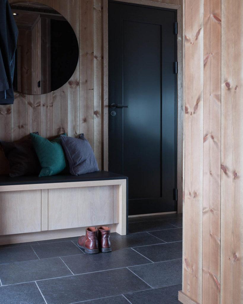 En moderne fjellhytte med mørke fiser av børstet Ottaskifer i gulvet på entreen i kombinasjon med treverk. På gulvet står ett par sko,
