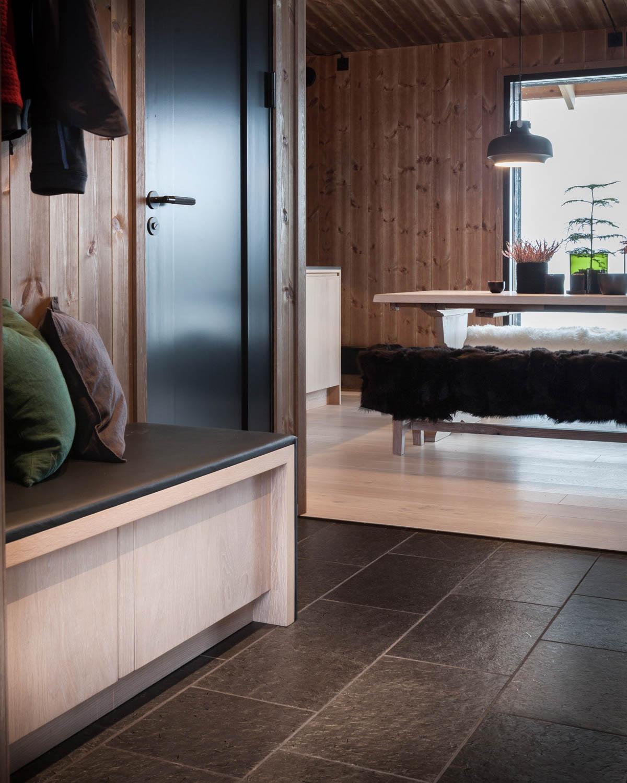 En moderne fjellhytte med mørke fiser av børstet Ottaskifer i gulvet på entreen i kombinasjon med treverk. Man ser innover til stuen.