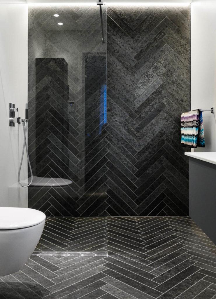 Et moderne bad med sort Ottaskifer flis på vegg og gulv i fiskebensmønster