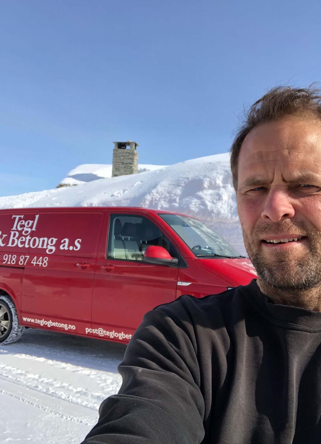 Et portrett av Cato Hetland som står foran sin arbeidsbil og høye brøytekanter
