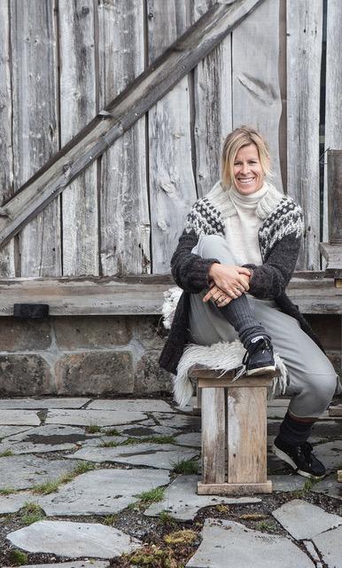 Et portrett av Mariann Vigtel Holland som sitter utenfor en hytte med skifer på grunnmur og på bakken