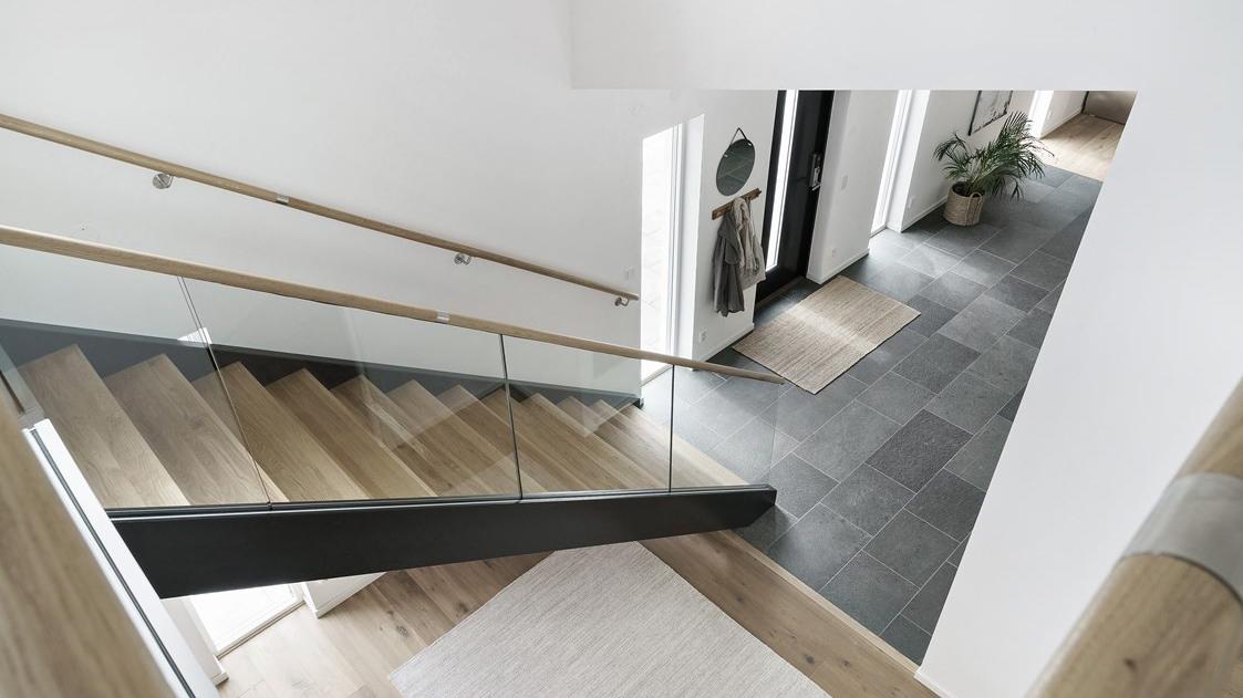 En tretrapp som går ned til en entré som er belagt med grå fliser i skifer fra Offerdal- Huset har en types skandinavisk stil.