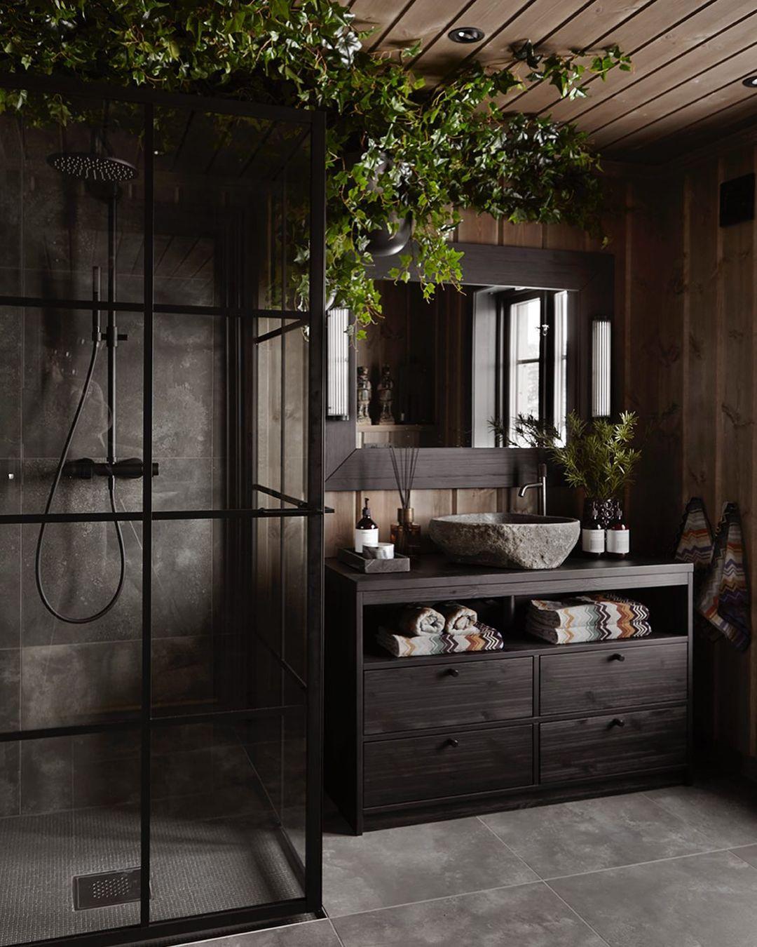 Mørkt hyttebad med grå skiferflis på gulv og i dusjveggen, og mørk treinnredning
