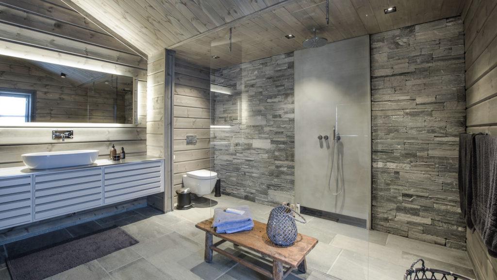Et stort bad med en dusjvegg i lys Oppdal skifer murstein med en støpt plate på midten der dusjhodet er festet. Lys Oppdal skfier fliser på gulvet. En stor vask er langs ene veggen.