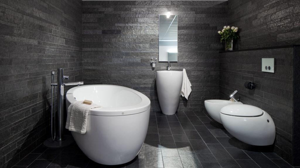 Et bad med smale fliser, strips, av Ottaskifer på  vegg og gulv. Badet har vask, toalett, bidet og badekar fra Alessi.