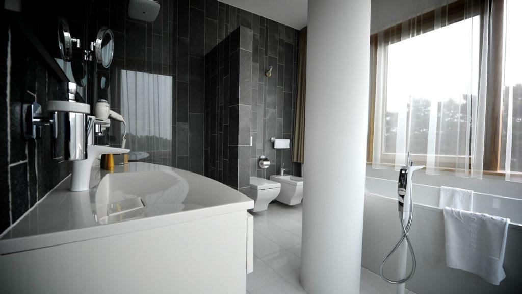 Et stort bad med luksusfølelse med fliser på veggen av fliser av skifer fra Offerdal i kombinasjon med hvit marmor på gulvene. Badet er stort og ligner en relax avdeling